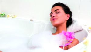 Eine Dame badet entspannt in einem Schaumbad.